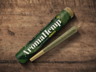 A top-down shot of an AromaHemp preroll on a wood table laying next to its container tube