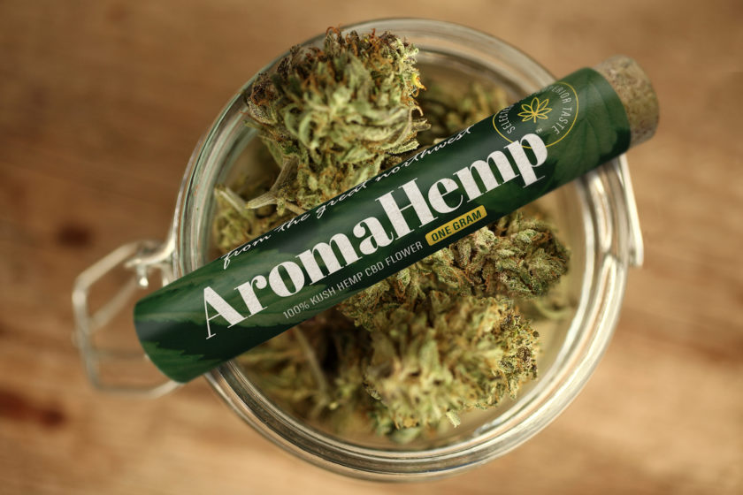 An AromaHemp preroll tube sitting on a jar of kush hemp